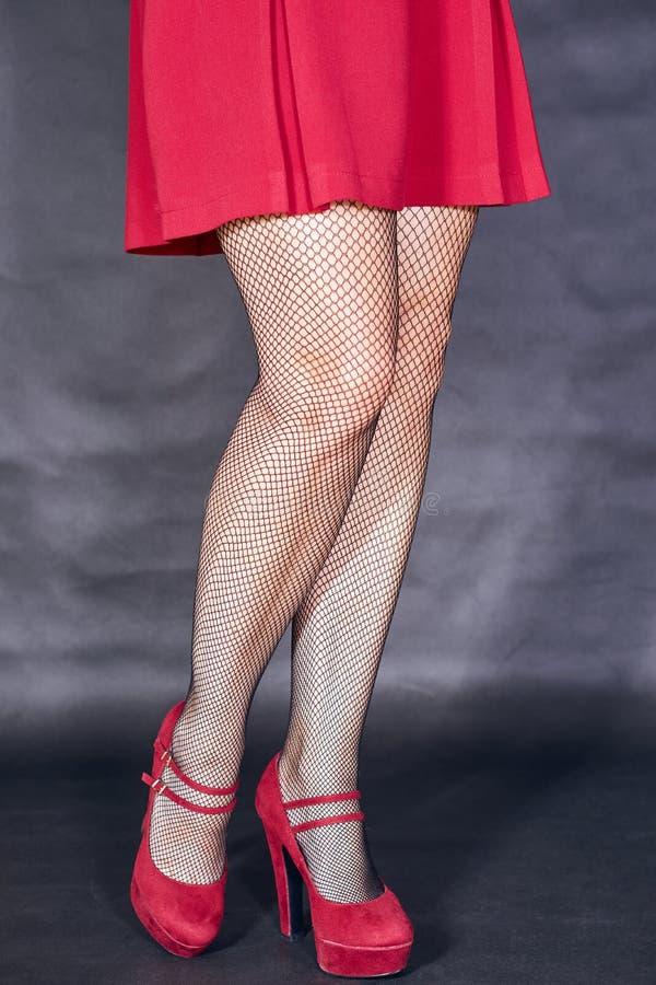 Les jambes de la fille en robe rouge images stock