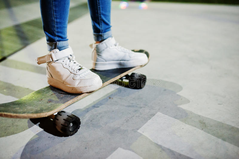 Les jambes de la fille urbaine adolescente sur la planche à roulettes au patin se garent sur l'ev photographie stock libre de droits