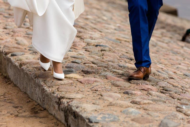 Les jambes de la promenade de jeunes mariés dans des chaussures photographie stock
