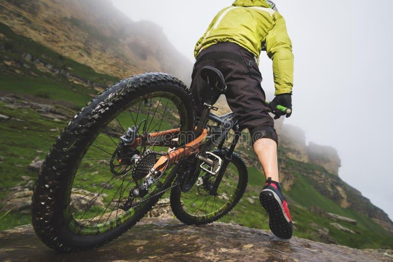 Les jambes de la vue en gros plan de cycliste et de roue arrière du mtb arrière font du vélo en montagnes sur le fond des roches  image libre de droits