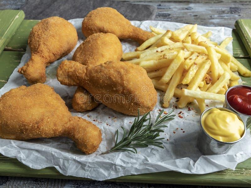 Les jambes de poulet frit croustillantes ont pané la couleur d'or, pommes frites, sauce, fond en bois photos stock