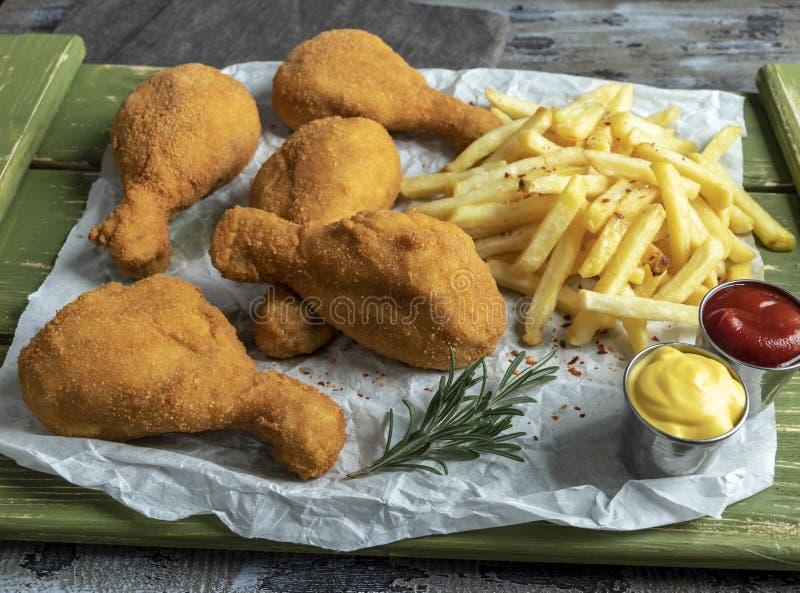 Les jambes de poulet frit croustillantes ont pané la couleur d'or, pommes frites, sauce, fond en bois photographie stock