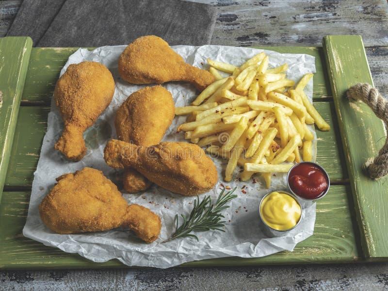Les jambes de poulet frit croustillantes ont pané la couleur d'or, pommes frites, sauce, fond en bois photographie stock libre de droits