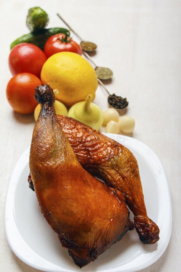 Les jambes de poulet ont fait cuire sur un gril et des légumes organiques frais sur un fond blanc Viande croustillante pour le dé images stock