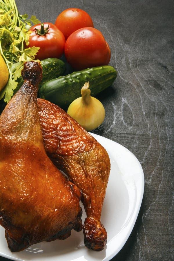 Les jambes de poulet ont rôti sur un barbecue et des légumes organiques frais sur un fond noir Copiez l'espace aliments diététiqu images stock