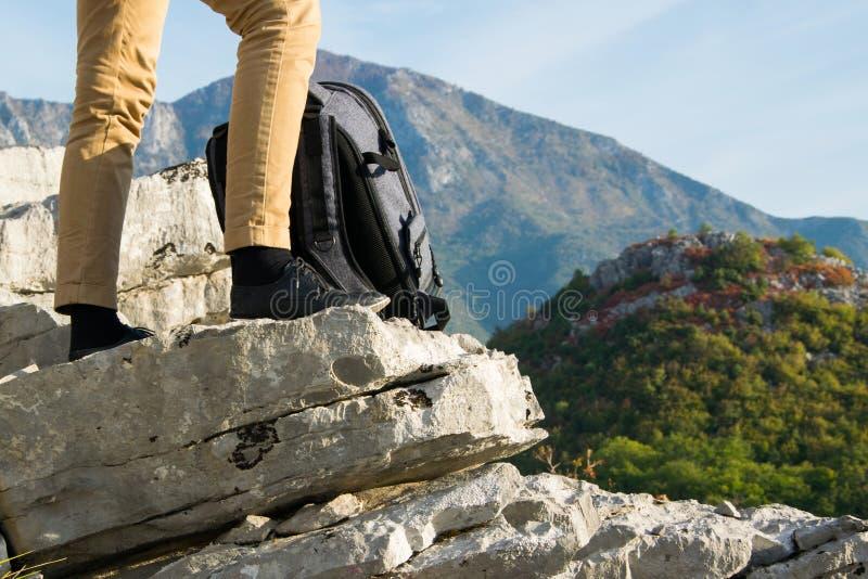 Les jambes de randonneur de femme se tient au bord de la falaise de montagne contre la belle crête de montagnes photos stock