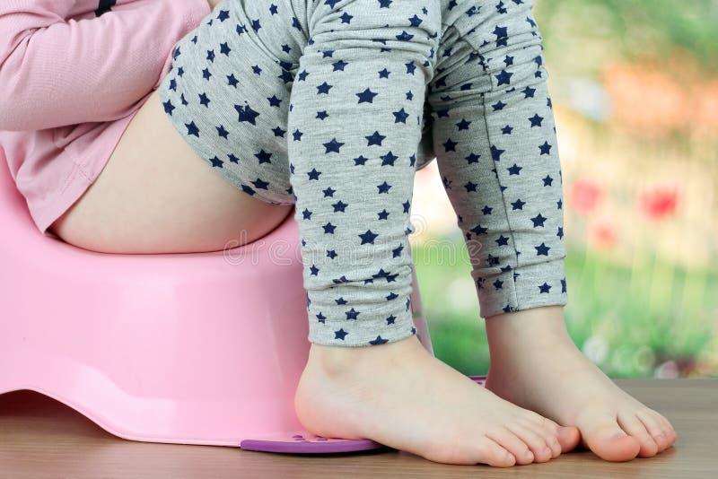 Les jambes des enfants pendant vers le bas d'un chambre-pot sur un backg vert photographie stock