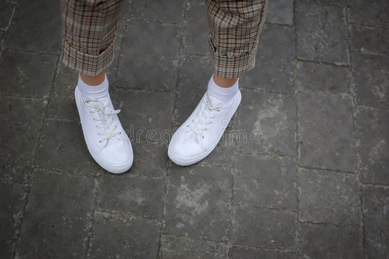Les jambes des femmes avec les espadrilles et le pantalon blancs de bringht sur la route pendant l'heure de ressort ou d'été deho images stock