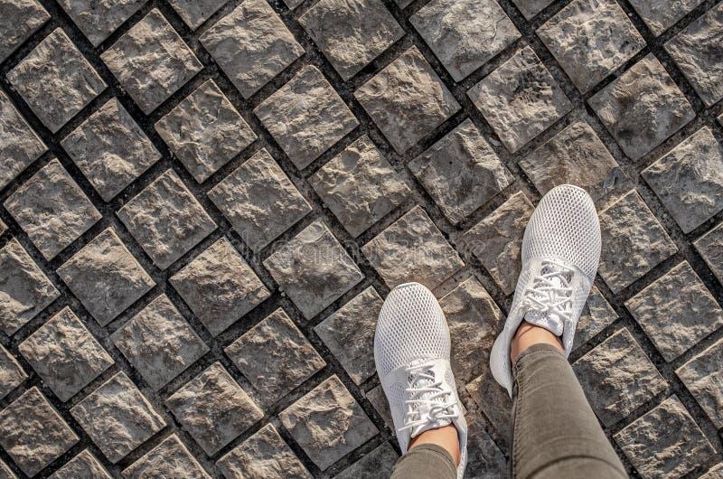 Les jambes des femmes dans des espadrilles blanches sur le trottoir photos stock