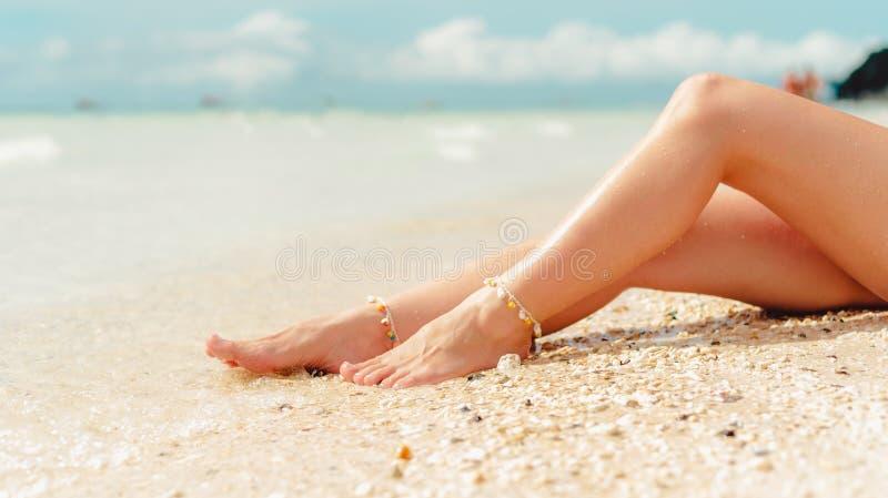 Les jambes des femmes les vacances d'?t? blanches de plage de sable photo stock