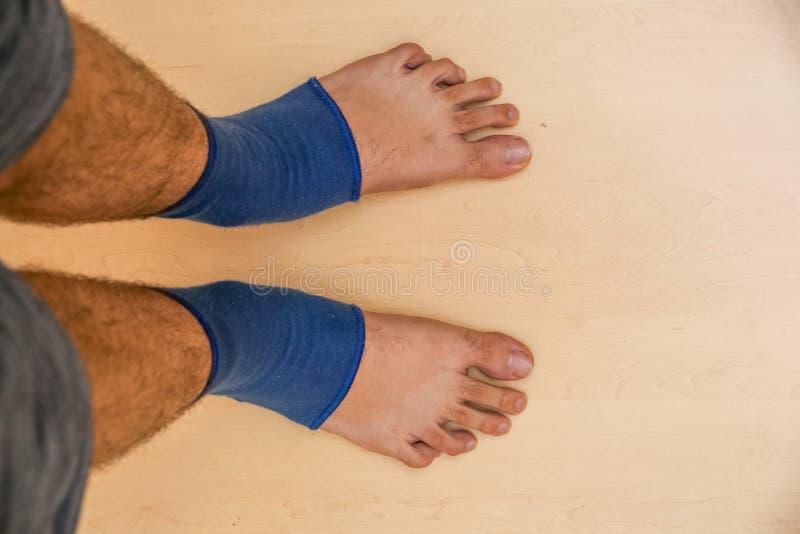 Les jambes des hommes après la parésie des extrémités inférieures avec un bandage médical bleu spécial Vue de ci-avant photos libres de droits