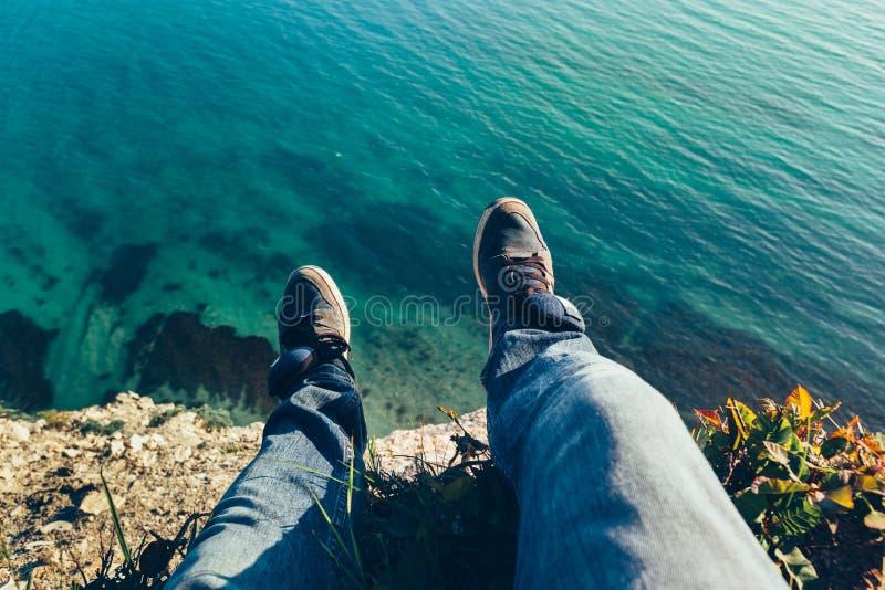Les jambes des hommes dans des espadrilles à l'arrière-plan du concept de détente landscapehiking de voyage de mer pittoresque image stock