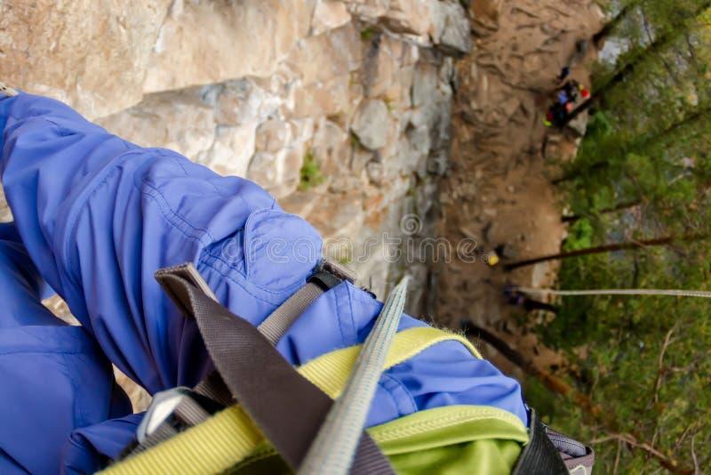 Les jambes du grimpeur accrochant sur une corde dans un harnais, première vue de personne de haut en bas photographie stock