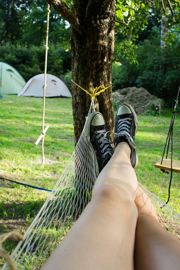 Les jambes du ` s de femmes dans des chaussures noires et blanches ont décrit le repos dans un hamac images libres de droits