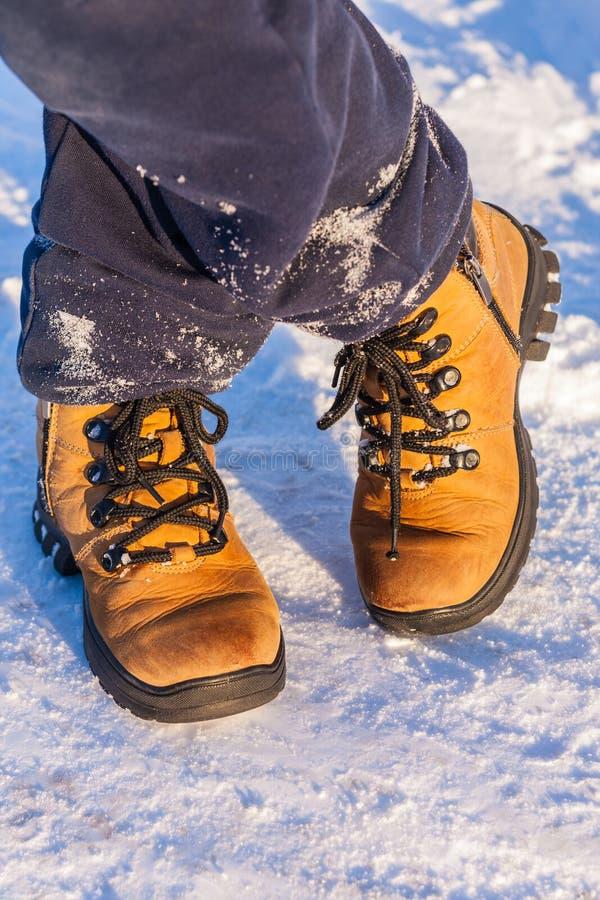 Les jambes du ` s de garçon dans les bottes se tenant sur la neige photos stock