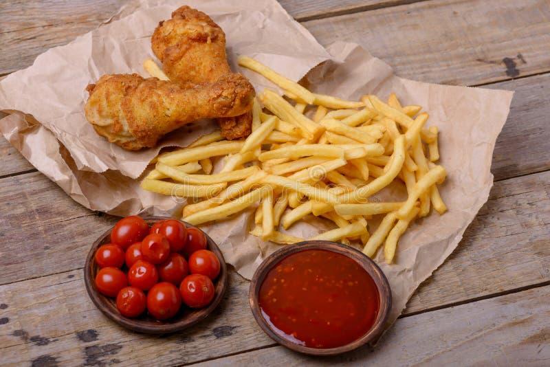 Les jambes et le ketchup de poulet croustillants avec garnissent images libres de droits