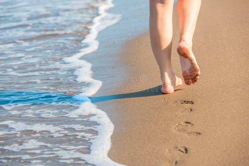 Les jambes femelles bien faites laissent des empreintes de pas sur un sable images libres de droits