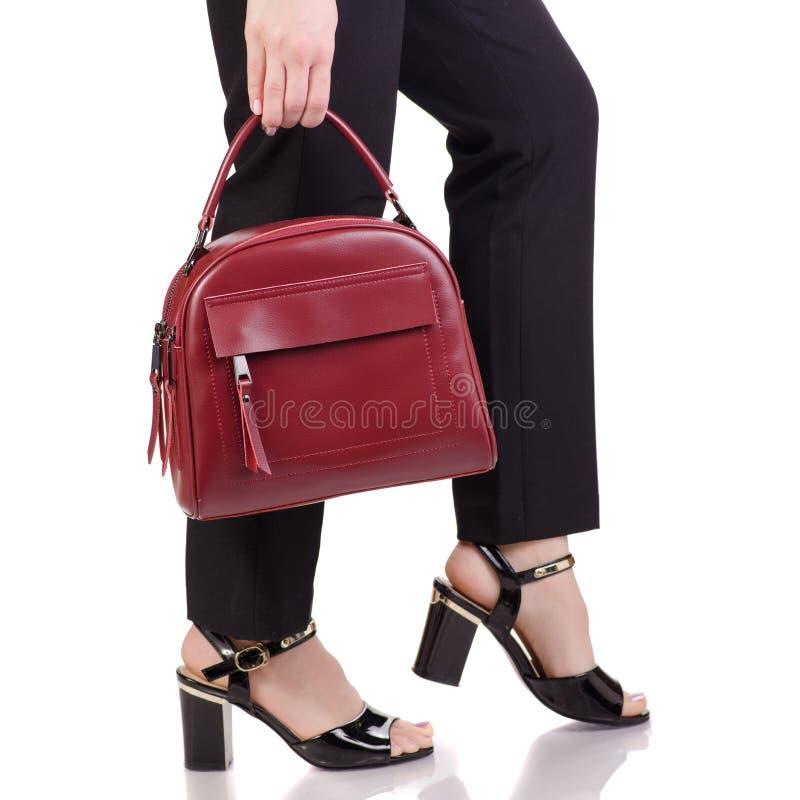 Les jambes femelles dans le noir classique halète les chaussures noires de laque avec le sac à main en cuir rouge à disposition photo stock