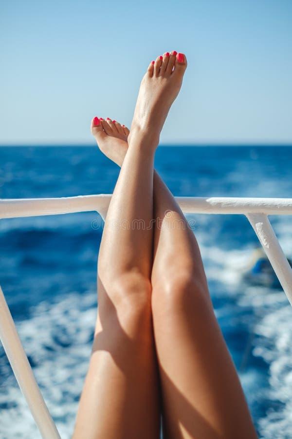 Les jambes femelles se sont penchées sur la barrière de bateau avec des vagues de mer derrière photographie stock libre de droits