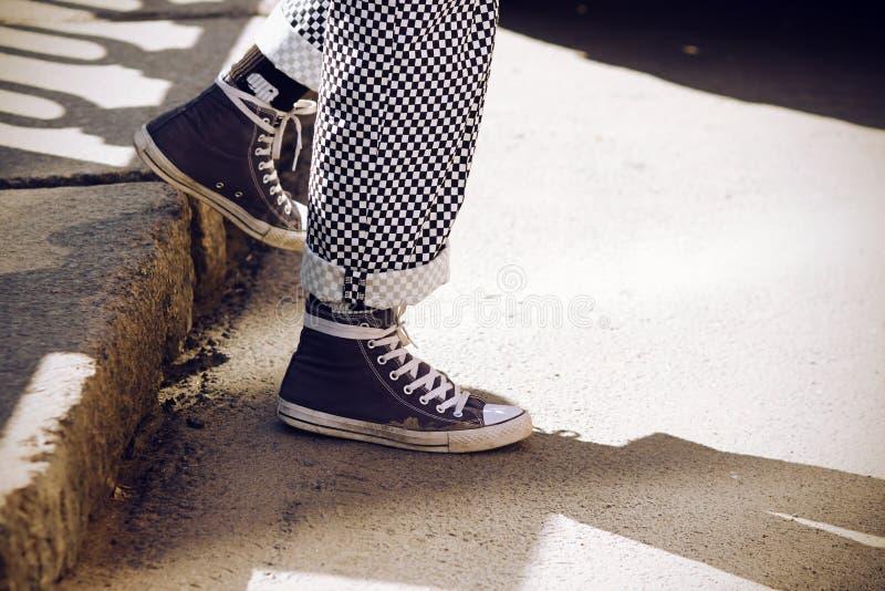Les jambes habillées dans le pantalon de plaid et dans des espadrilles bleues descendent de l'étape images libres de droits