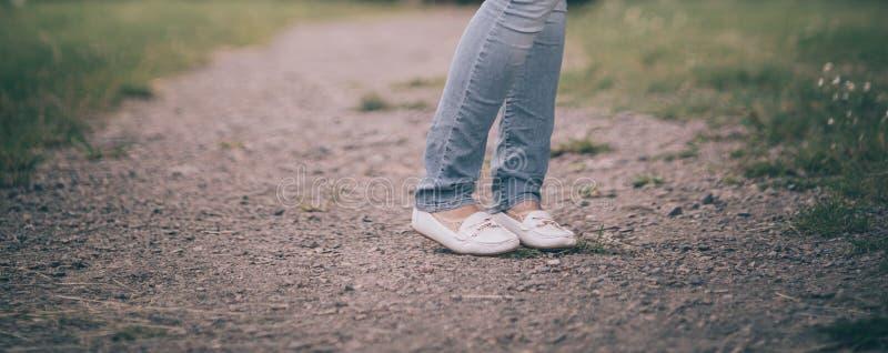 Les jambes se ferment  jeune femme avec le parapluie se tenant sur le chemin en parc photos stock