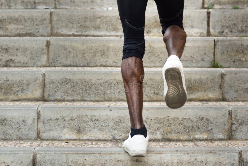 Les jambes sportives de l'homme de couleur fonctionnant sur l'escalier fait un pas photos stock