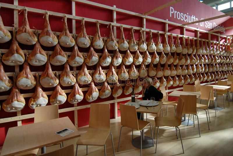 Les jambons crus italiens de San Daniele de spécialité de nourriture ont accroché dans un support juste de nourriture photo stock