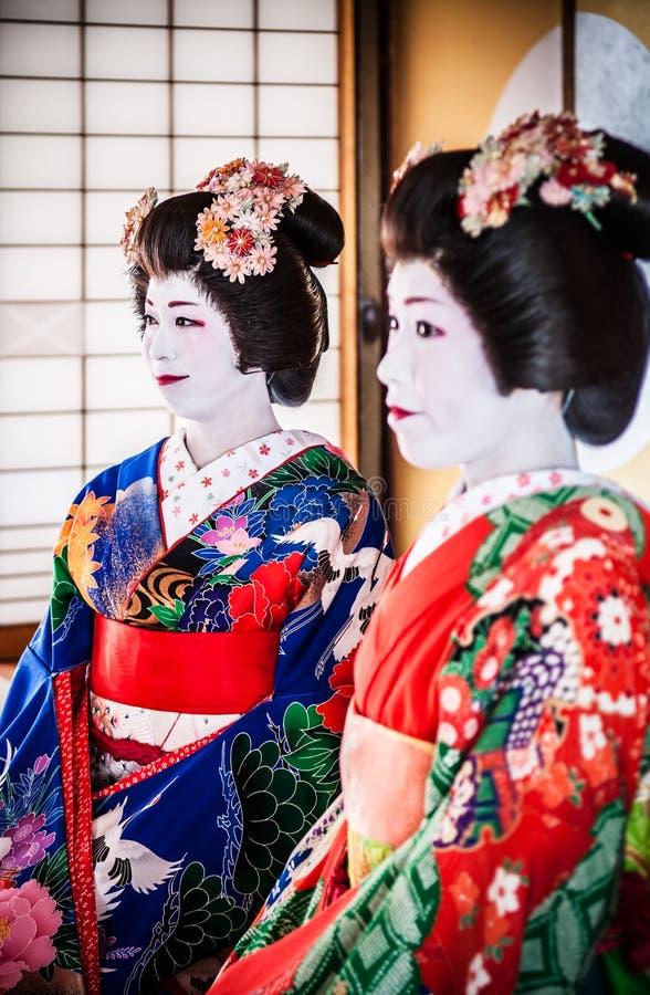 Les Japonais Maiko, geisha dans le costume rouge et bleu s'asseyent dans le traditiona photos libres de droits