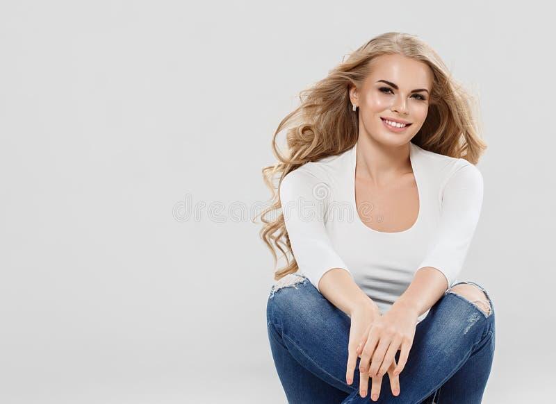 Les jeans blonds de cheveux bouclés de belle femme façonnent la séance intégrale sur le plancher photographie stock