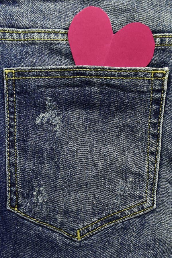 Les jeans donnent une consistance rugueuse avec le coeur rose à l'intérieur de la poche photographie stock libre de droits