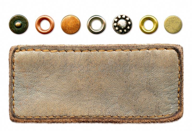 Les jeans en cuir étiquettent et un ensemble de rivets en métal images libres de droits