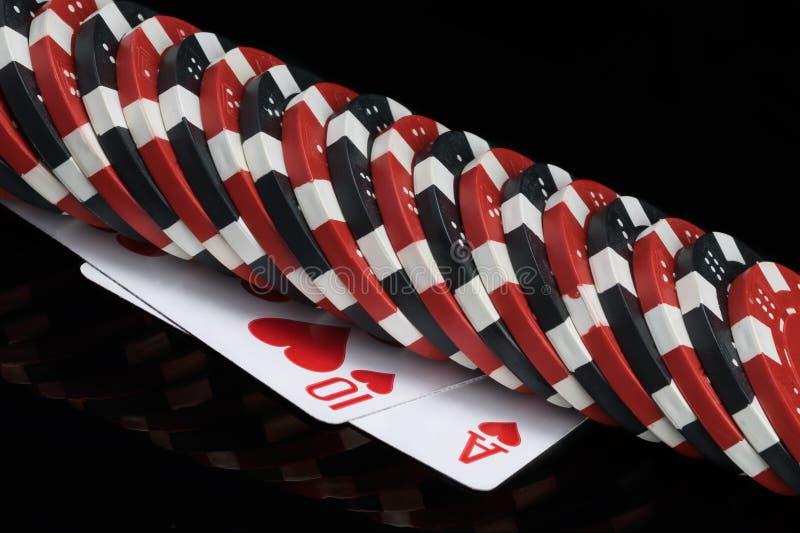 Les jetons de poker se situent dans une rangée sur deux cartes de jeu, fond noir image stock