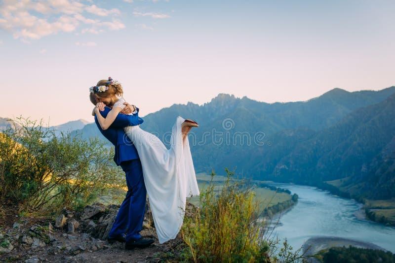 Les jeunes ?pousent nouvellement des couples, baisers de jeunes mari?s, ?treignant sur la vue parfaite des montagnes, de la rivi? images stock