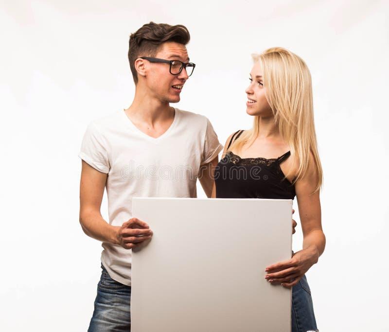 Les jeunes étonnés couplent montrer la présentation dirigeant la plaquette photos stock