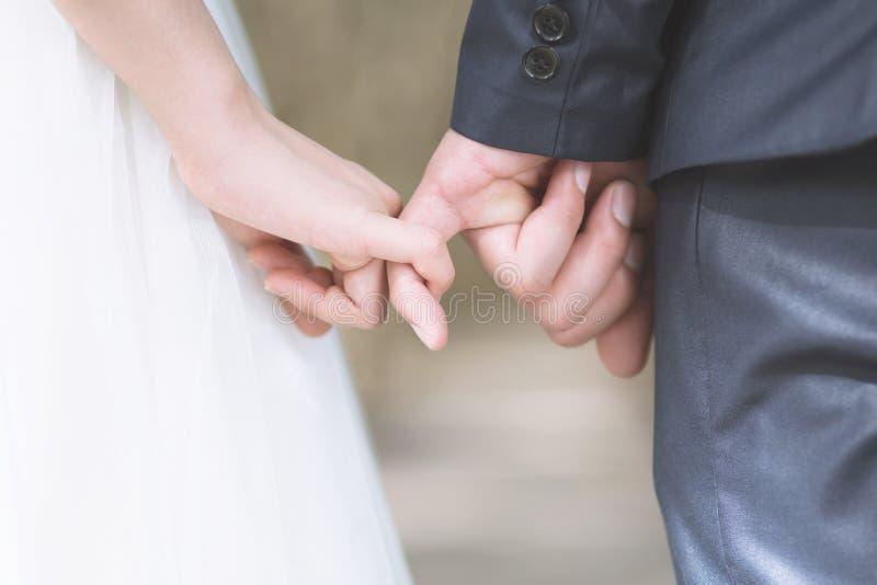 Les jeunes affectueux aiment les couples mariés tenant des mains et se tiennent ensemble dans le jour du mariage de cérémonie photographie stock