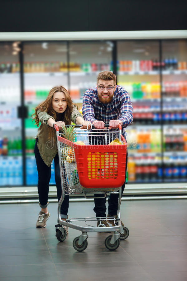 Les jeunes ajouter heureux à la nourriture transportent en charrette faire des achats d'épiceries photo libre de droits