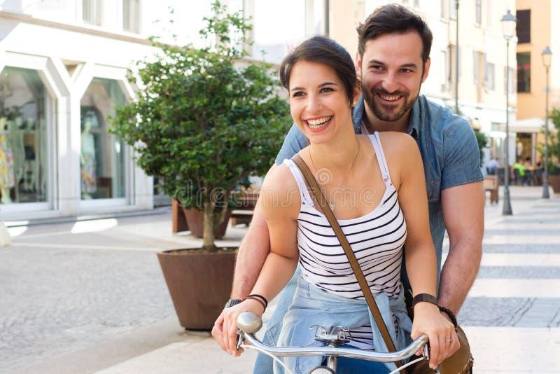 Les jeunes amants couplent monter une bicyclette dans la rue image stock
