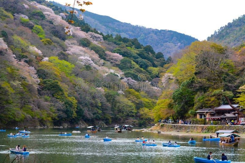 Les jeunes amants et familles barbotent des bateaux à rames vers le haut de Katsura River à Kyoto pour apprécier les fleurs de ce photographie stock libre de droits