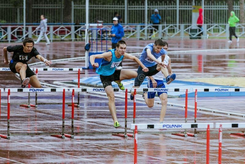 Les jeunes athlètes courent des obstacles de 110 mètres sous la pluie photo libre de droits