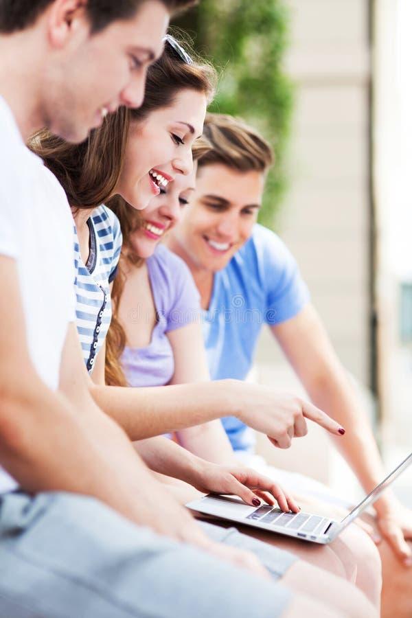 Les jeunes avec l'ordinateur portatif photographie stock
