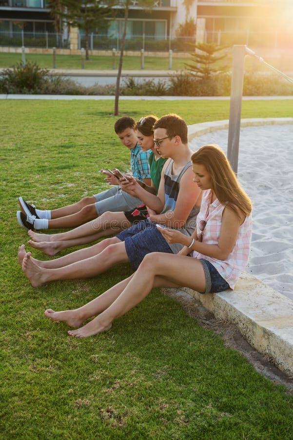 Les jeunes avec les dispositifs numériques photographie stock libre de droits