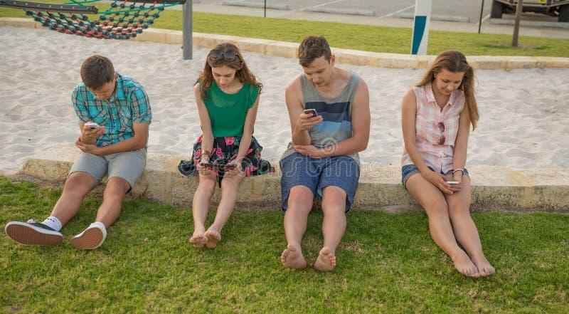 Les jeunes avec les dispositifs numériques image libre de droits
