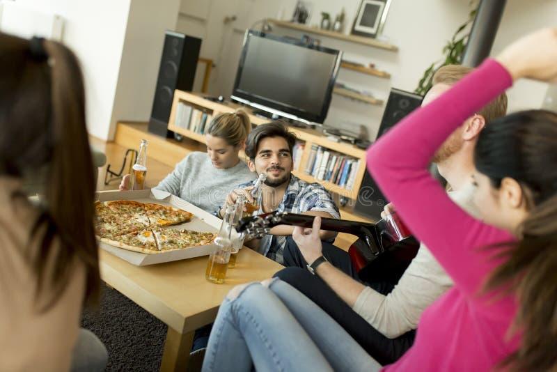 Les jeunes ayant la partie de pizza dans la chambre image libre de droits