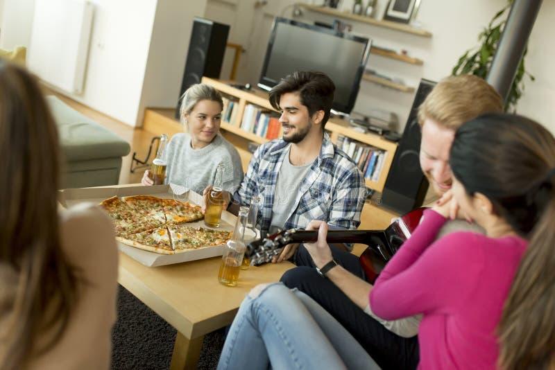 Les jeunes ayant la partie de pizza dans la chambre images libres de droits