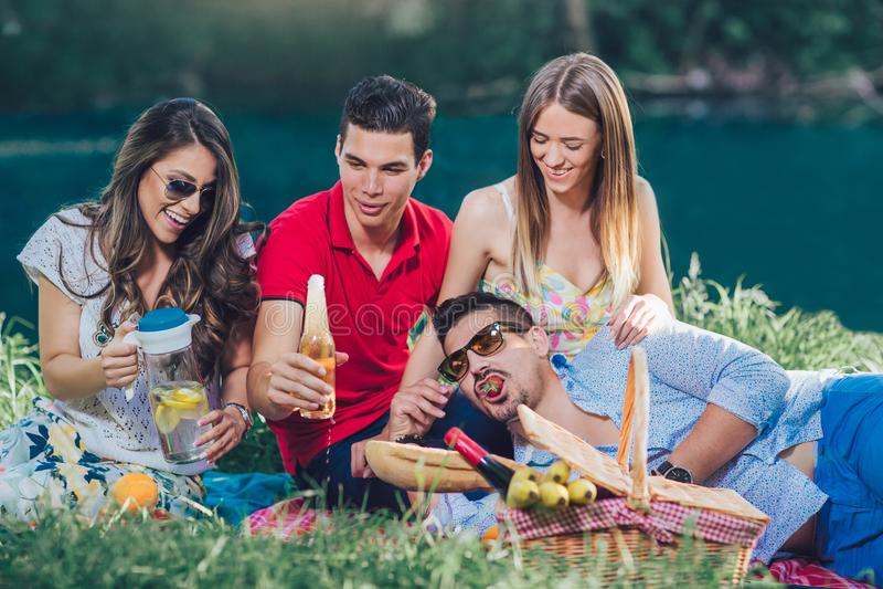 Les jeunes ayant le pique-nique près de la rivière photos stock