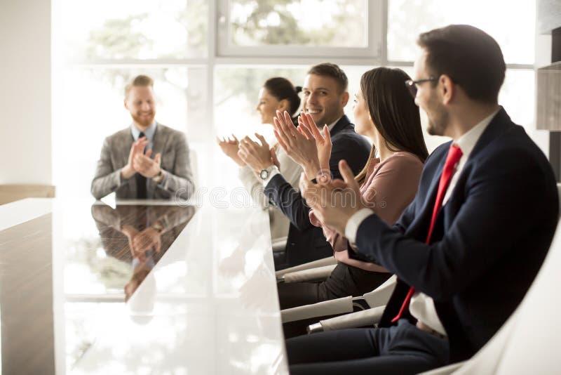 Les jeunes ayant une réunion dans le bureau images stock