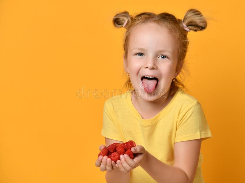 Les jeunes baies de prise d'enfant de bébé dans des mains ont étonné des cris riants heureux sur le jaune photo libre de droits
