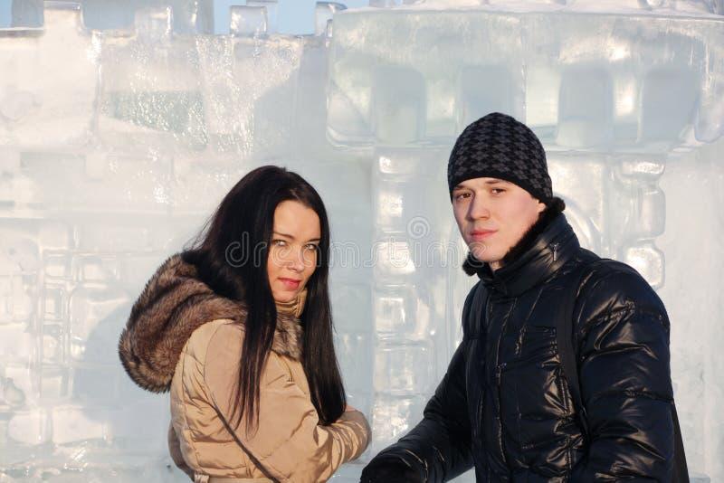 Les jeunes beaux couples s'élèvent le mur ordonné de glace à l'hiver images stock
