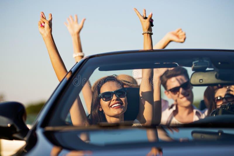 Les jeunes belles jeunes femmes aux cheveux foncés avec des amis dans des lunettes de soleil sourient et montent dans un cabriole images stock