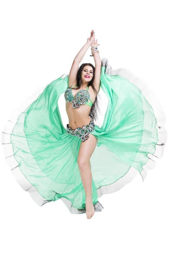 Les jeunes belles femmes orientales exotiques exécute la danse de ventre dans la robe verte ethnique D'isolement sur le fond blan image libre de droits